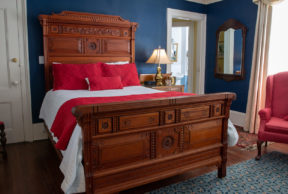 The Victoria Room at The Cuthbert House Inn boasts rich blue walls, red accents, and a comfortable bed.