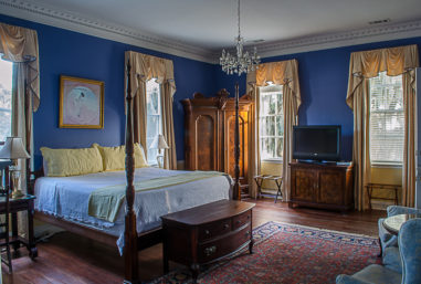 An elegant room boasts antiqued furniture, hardwood floors, vaulted ceilings, and a four poster bed.